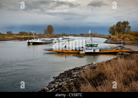 The Netherlands, near Doesburg, Cargo boat and car ferry on IJssel river. - Stock Photo