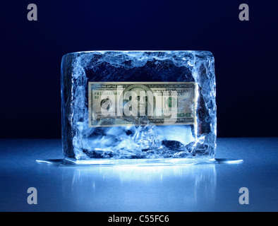 Large block of ice with one hundred dollar bill frozen inside - Stock Photo