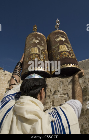 Orthodox Jew wrapped with Talit ( prayer shawl ) holding Torah sacred scrolls at the Western Wall East Jerusalem - Stock Photo