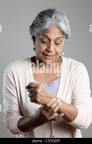 Senior woman suffering with pain in her wrist - Stock Photo
