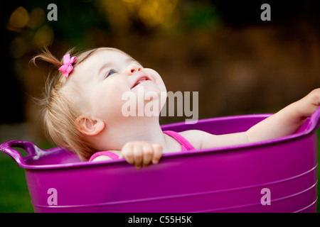 Baby girl playing in a bathtub and smiling, Traverse City, Grand Traverse County, Michigan, USA - Stock Photo