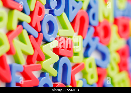 Plastic fridge magnets on white background. Short depth of field. - Stock Photo