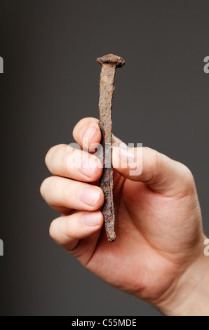 Man holding an old rusty nail in his hand - Stock Photo