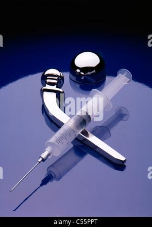 Titanium artificial hip and syringe on shiny blue background, studio shot - Stock Photo
