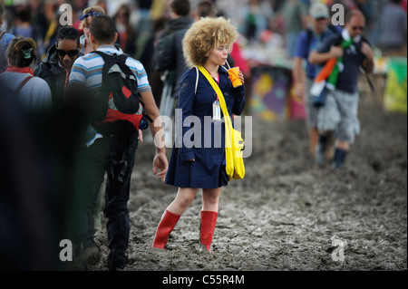 A girl in red wellington boots tackling the mud at the Glastonbury Festival 2011 - Stock Photo