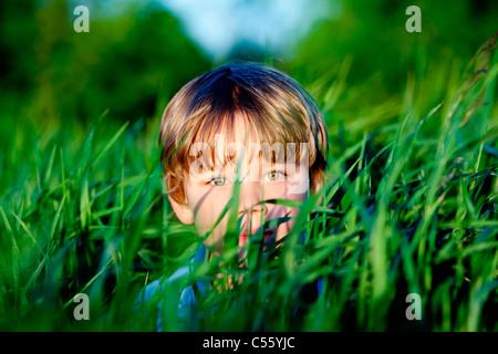 Boy hiding in grass - Stock Photo