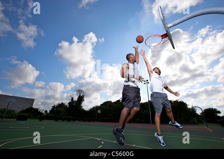 male scoring during outdoor basketball game of two on two - Stock Photo