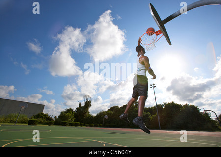 male making slam dunk during outdoor basketball game, upward view - Stock Photo