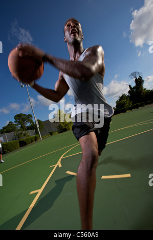 male driving during outdoor basketball game - Stock Photo