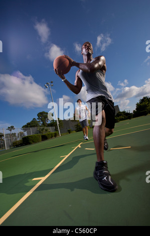 males playing outdoor basketball game, one driving to basket - Stock Photo