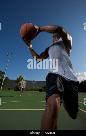 males playing outdoor street basketball with one player driving to basket - Stock Photo