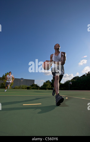 males playing outdoor street basketball with one driving to basket - Stock Photo