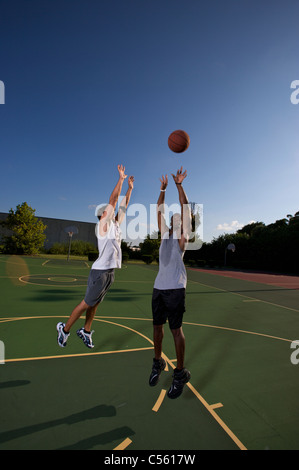 jump shot during two on two basketball game being defended - Stock Photo