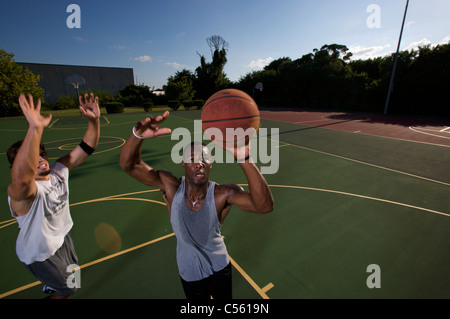 males playing outdoor basketball game - Stock Photo