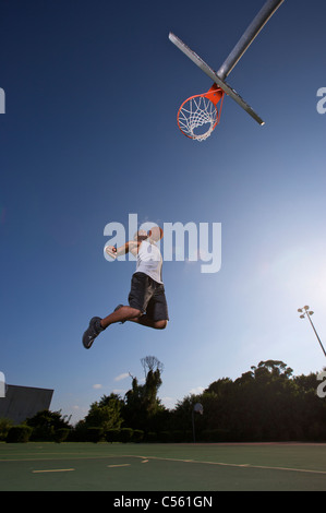 male making slam dunk during outdoor basketball game - Stock Photo