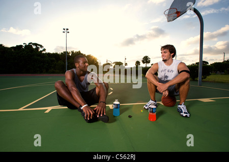 males resting, relaxing after after playing basketball on outdoor court, dramatic sky - Stock Photo