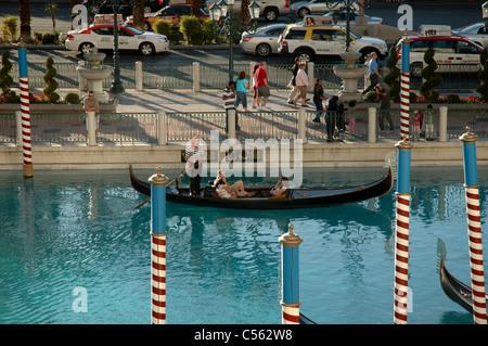 A gondolier steers a gondola through the canal in the Venetian hotel alongside Las Vegas Boulevard in Las Vegas, - Stock Photo