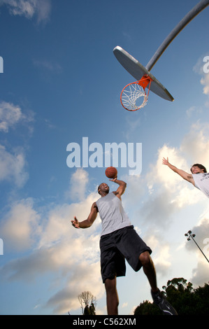 male scoring during outdoor basketball game, looking upward toward goal - Stock Photo