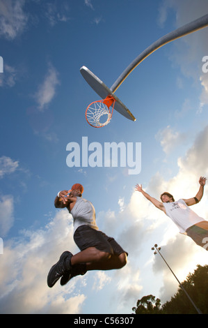 male scoring during outdoor basketball game, upward angle toward goal - Stock Photo