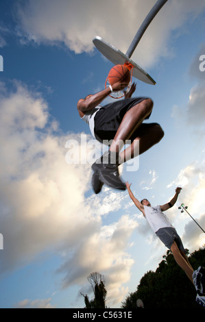 male scoring during outdoor basketball game, viewed from underneath - Stock Photo