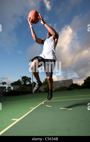 male making vertical jump during outdoor basketball game - Stock Photo