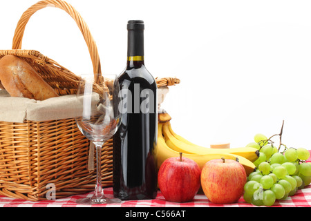 Picnic basket with healthy food and wine on white background. - Stock Photo