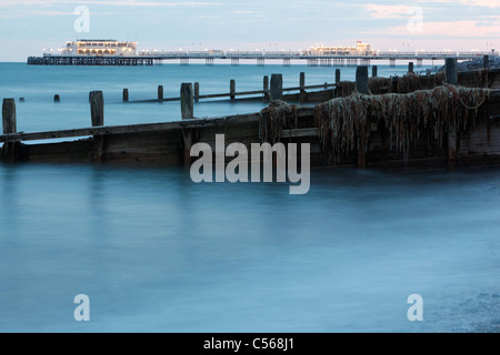 Worthing pier and groyne sea defences covered in seaweed from the beach in the evening light - Stock Photo