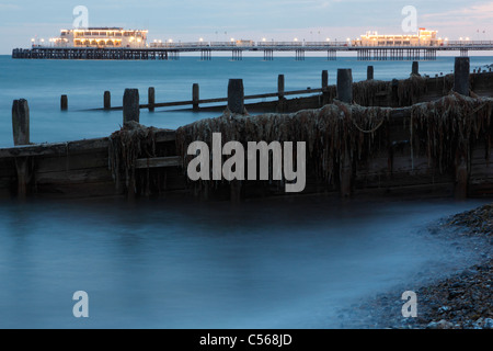 Worthing pier and wooden groyne sea defences covered in seaweed from the beach in the evening light - Stock Photo