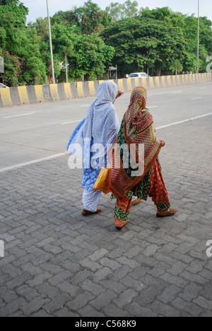 two women walking road - Stock Photo