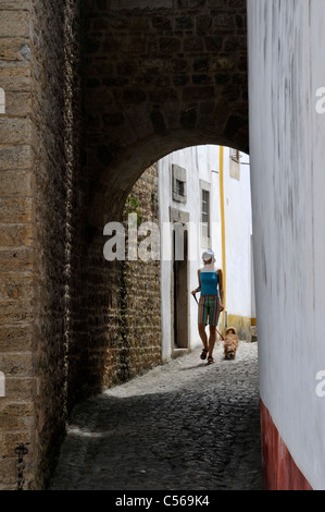 Obidos, Portugal: girl with dog in a typical street. - Stock Photo