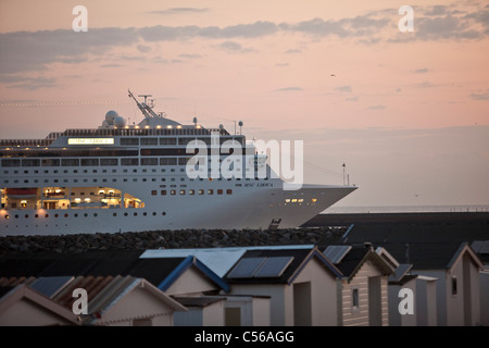 The Netherlands, IJmuiden, Cruise ship arriving at North Sea Canal. Sunrise. Beach cabins. - Stock Photo