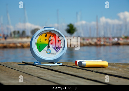 HIgh sun UV index reading on a sunny July afternoon on a landing stage at the beach. The recommended sunscreen is - Stock Photo