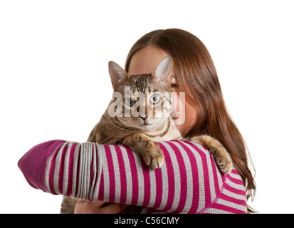 Bengal cat sits on shoulder of young woman and stares at camera in isolated studio shot showing love between pet - Stock Photo