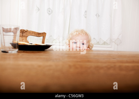 A young toddler peeking over the edge of the table before meal time - Stock Photo