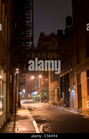 Alleyway with sky bridge and water tower in lower Manhattan at night after a rainstorm, New York City, USA. © Craig - Stock Photo