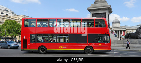London West End street scene side view of red unmarked public transport double decker London bus passing Nelsons - Stock Photo