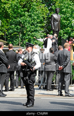 Armed police officer at unveiling ceremony for President Ronald Reagan bronze statue at American Embassy Grosvenor - Stock Photo