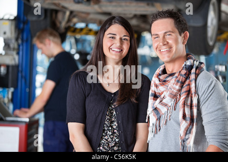 Portrait of smiling young couple in auto repair shop with mechanic in the background - Stock Photo