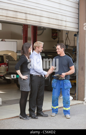 Full length of mechanic shaking hands with client outside garage - Stock Photo