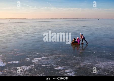 The Netherlands, Marken, Children with sledge ice skating on frozen lake called IJsselmeer. - Stock Photo