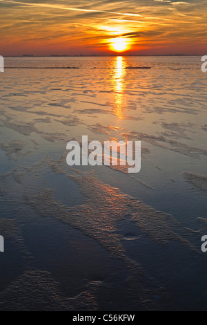 The Netherlands, Marken, Frozen lake called IJsselmeer. Sunset. - Stock Photo