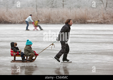 The Netherlands, Ankeveen. Man and two children on sledge ice skating. - Stock Photo
