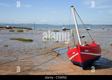 Beached red boat on the sands at low tide in Morecambe Bay, Lancashire, England, UK, Britain. - Stock Photo