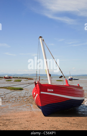 Beached red boat on Morecambe sands at low tide in Morecambe Bay, Lancashire, England, UK, Britain. - Stock Photo