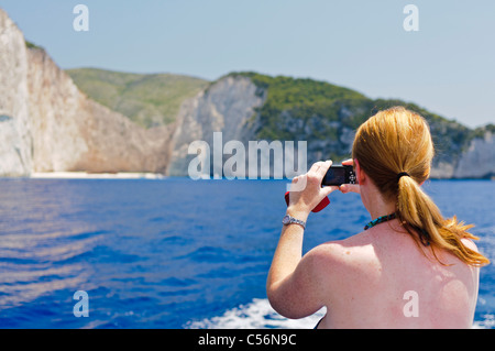 Woman takes a photograph of Navagio (Shipwreck) Bay from a boat - Stock Photo