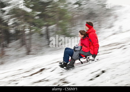 The Netherlands, Egmond aan Zee, Man and woman sledging. - Stock Photo