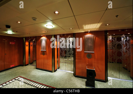 Ornate passengers lifts with mirror doors on Deck 12, Queen Mary 2 Ocean Liner. - Stock Photo
