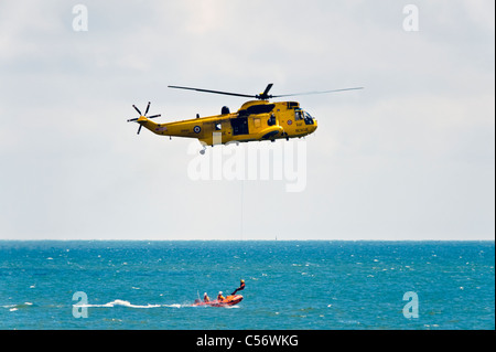 Search & rescue Sea King helicopter and RNLI lifeboat rescue at sea, National Air show, Swansea, Wales, UK. Winchman - Stock Photo