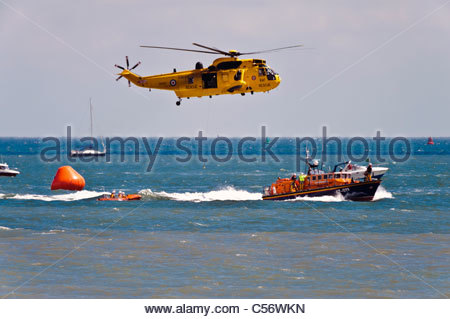Search & rescue Sea King helicopter and RNLI lifeboat rescue at sea, National Air show, Swansea, Wales, UK. - Stock Photo