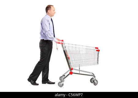 A full length portrait of a man pushing an empty shopping cart - Stock Photo